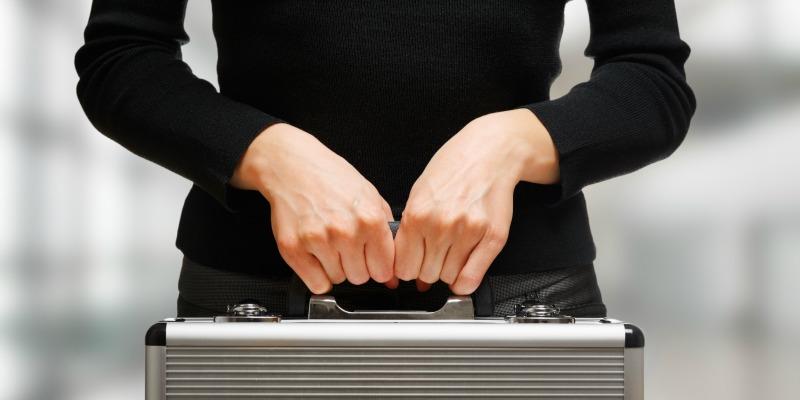 Business woman holding an aluminium briefcase.